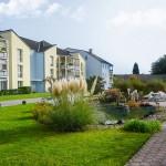 Wohnanlage Haus am Wald Ratingen - Grünanlage mit Teich und Blick auf die Vorderseite